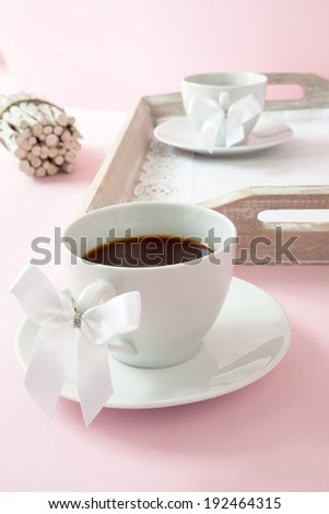 Coffee cups with ribbon on the handle - stock photo