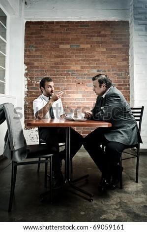 Coffee date debate between two men during their lunch break - stock photo