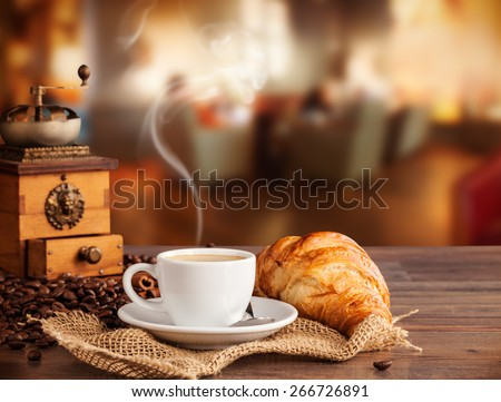 Coffee drink served with croissant on wooden table with blur cafeteria as background - stock photo