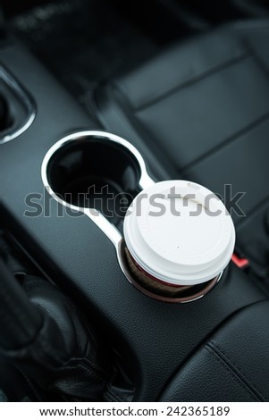 Coffee Drinking While Driving. Single Paper Coffee Cup Inside Car Cup Holder.  - stock photo
