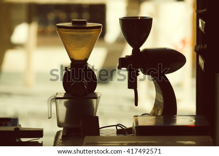 Coffee equipment concept. Vintage electrical coffee grinders in coffee shop standing on window with a street view. Close up - stock photo