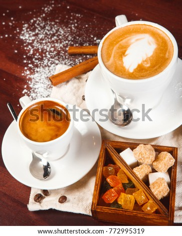 coffee - espresso and cappuccino in white cups on saucers with spoons on a tissue napkin, white and brown sugar, candied fruits in a brown wooden box, coffee beans, cinnamon sticks, powdered sugar