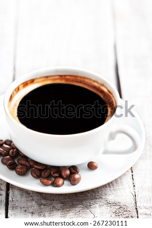 Coffee Espresso. Coffee cup with roasted coffee beans over white wooden table with copyspace. - stock photo