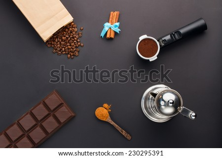 Coffee espresso in a holder, coffee-beans, bar of chocolate, cinnamon, coffee-pot - stock photo