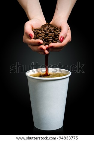 Coffee flows from a handful of beans into a paper cup - stock photo