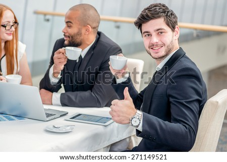 Coffee for a business meeting. Four confident successful businessmen at a meeting while sitting at a table discussing business affairs in the office and drinking coffee - stock photo