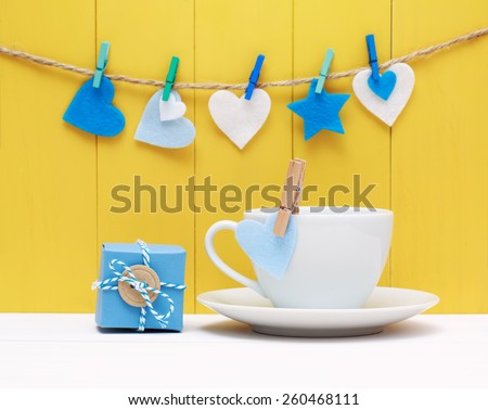 Coffee for a loved one or sweetheart decorated with pretty blue and white hearts hanging from clothes pegs over a yellow background of rustic wooden boards with a small gift box - stock photo