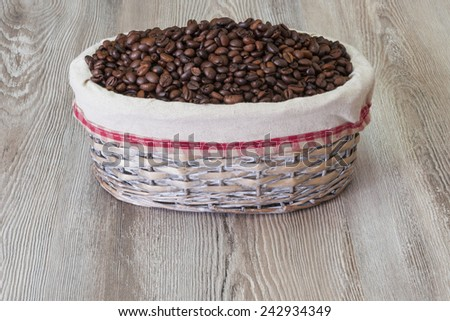 Coffee, fresh aromatic coffee beans in a wicker basket and jute, foreground.Coffee in of jute container on a wooden table - stock photo