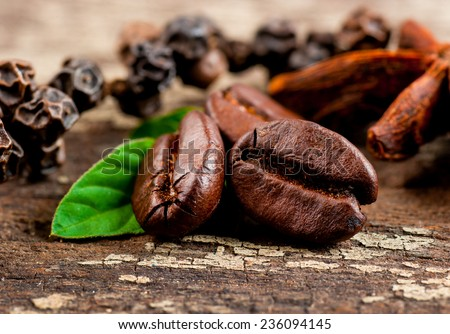 Coffee grains and green leaf on grunge wooden background - stock photo