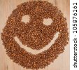 Coffee grains arranged in smiley. Isolated on wooden background. - stock photo