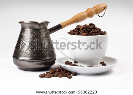 Coffee grains in a white cup and disseminated about a coffee pot on a light background
