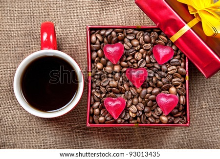 Coffee grains with heart shape candies in Red box with yellow ribbon and mug with black coffee at textured brown background on Valentines day