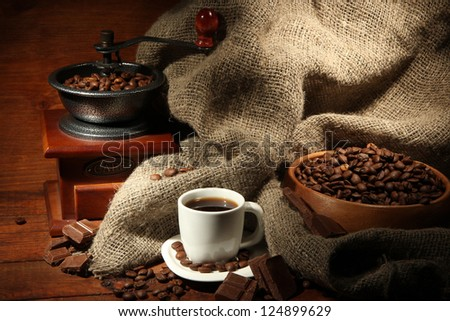 Coffee grinder and cup of coffee on brown wooden background