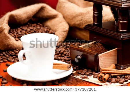 Coffee grinder and cup of coffee with spices on dark red background - stock photo