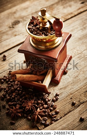Coffee grinder, coffee beans, cinnamon and anise on wooden background - stock photo