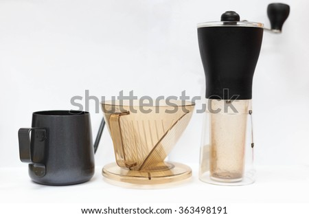 Coffee grinder , filter cup and small black pot isolated on white