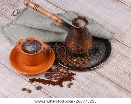 Coffee grinder, turk and cup of coffee on wooden background - stock photo