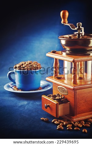 coffee grinder with beans and cup on saucer standing on blue table instagram stile instagram stile - stock photo