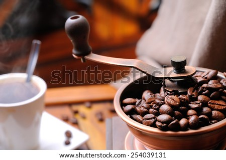 Coffee grinder with steaming coffee beans in the background close up - stock photo