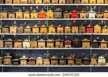 coffee grinders aligned in rows on store shelves, flea market Saint ouen, Paris, France. Retro collection of coffee grinders.  Bazaar retro wooden coffee grinders. Shop with antiques at the market. - stock photo