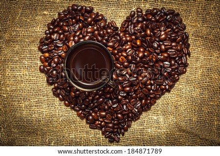 Coffee Heart made from beans lying on burlap with cup on it - stock photo