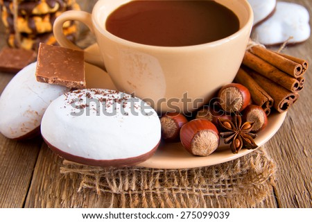 Coffee (hot chocolate) cup and gingerbread, cinnamon sticks, nuts, aroma spices and chocolate on rustic wooden table - stock photo