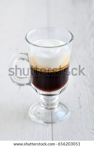 Coffee in a glass on a wooden table.