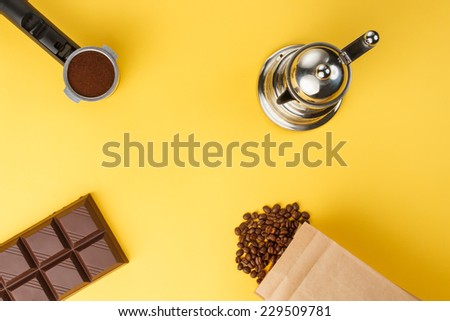 Coffee in a holder, coffee-beans, bar of chocolate, coffee-pot - stock photo