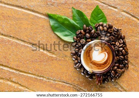 Coffee in a mug with beans &  leaves top view - stock photo
