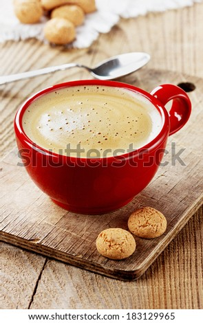 Coffee in a red cup with biscuit cookies on a rustic wooden board - stock photo
