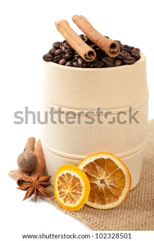 Coffee in a wooden barrel and spices: cinnamon, star anise and dried orange - stock photo