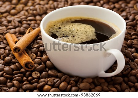 Coffee in beans with cinnamon sticks, studio shot
