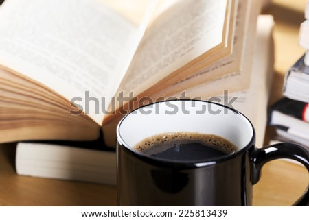 coffee in black cup and book pile - stock photo