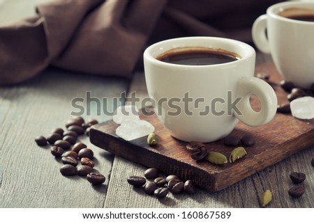 Coffee in cups with cardamom and white sugar on vintage wooden background - stock photo
