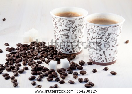 Coffee in paper cups with coffee beans and pieces of sugar - stock photo