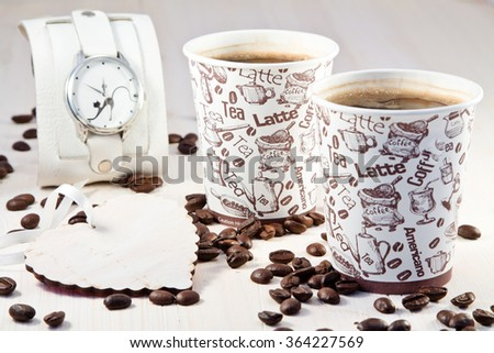 Coffee in paper cups with coffee beans, white heart and hours - stock photo