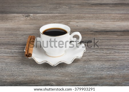 Coffee in porcelain cup and saucer with cinnamon and spoon - stock photo