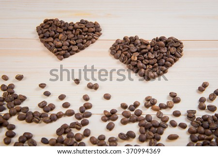 coffee in the shape of a heart on a wooden desk surface. coffee in the shape of a heart. Two hearts of coffee. Valentine's Day,  concept of love in hobby     - stock photo