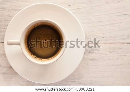 Coffee in white cup on white wood table - stock photo