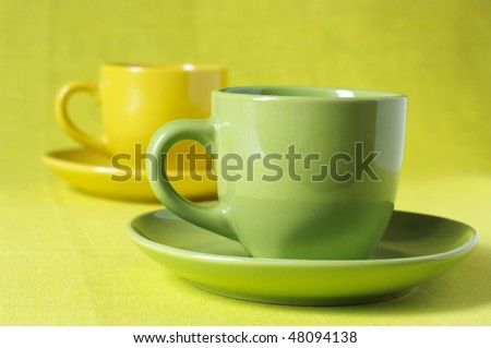 Coffee in yellow and green cups with saucers on lemon yellow linen cloth.