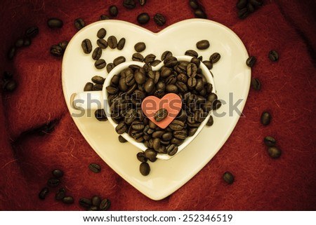 Coffee klatsch java concept. Heart shaped white cup filled with roasted coffee beans on red cloth background. Vintage filter - stock photo