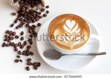 Coffee latte art and coffee beans on the table - stock photo