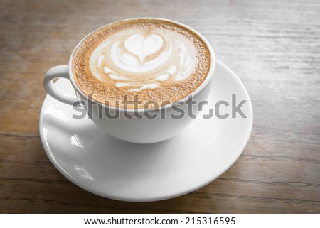 Coffee  latte art  at morning  on wood table in coffee shop
