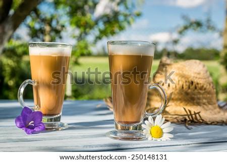 Coffee latte in a sunny garden - stock photo