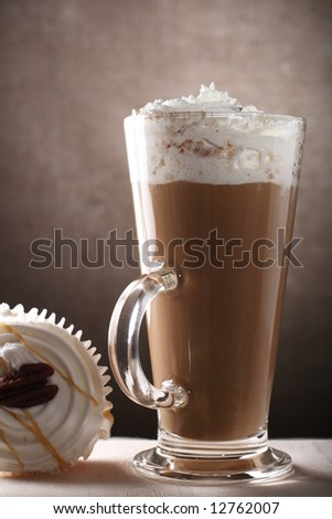 Coffee Latte in Tall Glass with sponge cup cake on brown rustic background, Low Key Lighting Technique - stock photo