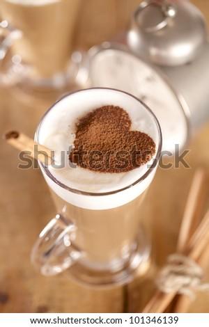 coffee latte with cinnamon sticks, focus on stiks end, , shallow dof - stock photo