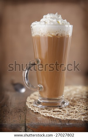 Coffee Latte with whipped cream in rustic style, shallow DOF, rough vignette for style - stock photo