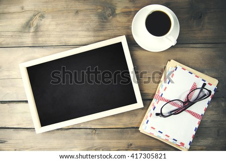 Coffee, letter,glasses and photo frames on wooden table