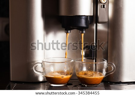 Coffee machine brewing a coffee espresso in home, two glass cups - stock photo