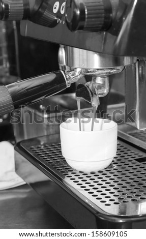 coffee machine making a cup of coffee in black and white